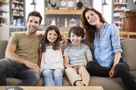 portraet der gluecklichen familie sitzend auf