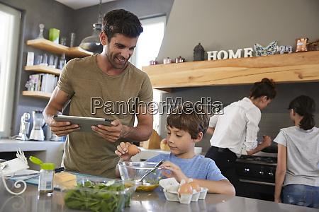 family in kitchen following recipe on