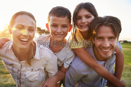 young couple piggybacking their kids outdoors
