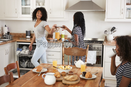 three teenage girls clearing table after