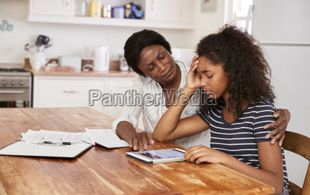 mother helps stressed teenage daughter with