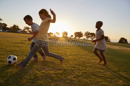 three children playing football in a