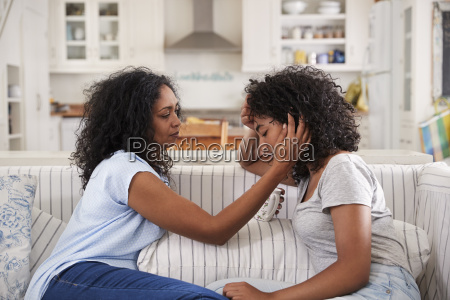 mother talking with unhappy teenage daughter