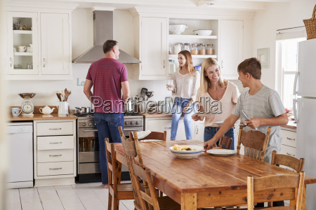 family with teenage children laying table