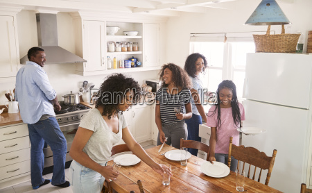 family with teenage daughters laying table