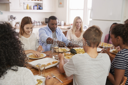 two families enjoying eating meal at