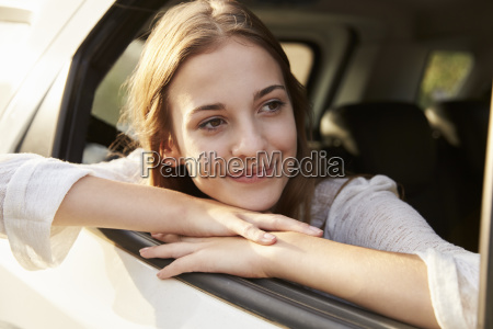 teenage girl looking out of car