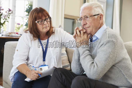 support worker visits senior man suffering