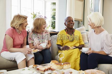 senior female friends enjoying afternoon tea