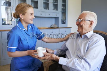 nurse giving senior man cup of
