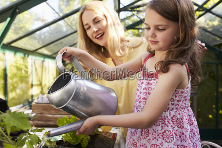 mother and daughter watering hanging basket