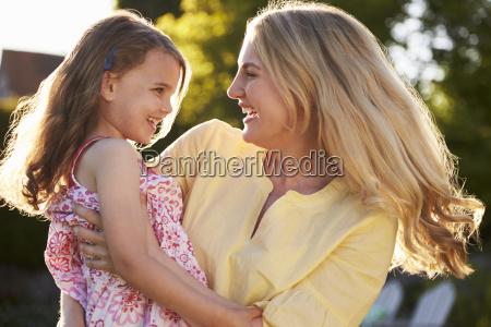 mother hugging daughter outdoors in summer