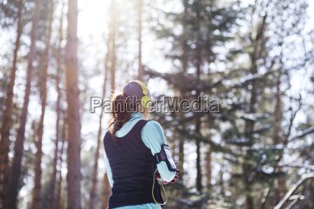 rueckansicht des jungen joggers mit kopfhoerern