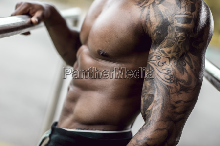 tattooed biceps of physical athlete close