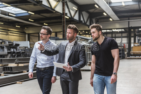 three men with tablet walking and