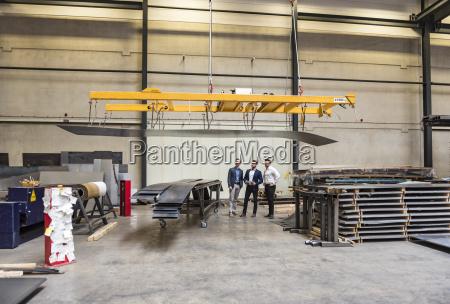three men standing on factory shop