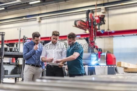 three men sharing tablet on factory