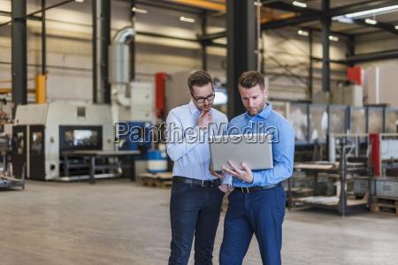 zwei geschaeftsmaenner die laptop auf fabrikarbeitsboden