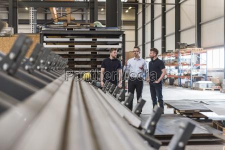 three men talking on factory shop