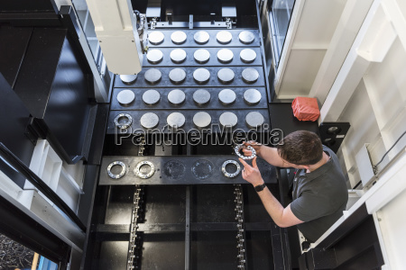 man examining workpiece in factory