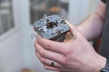 close up of man holding workpiece