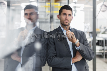 businessman leaning against glass pane in