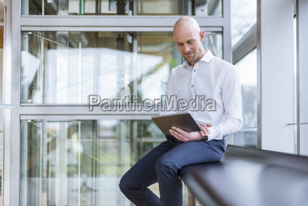 smiling businessman sitting at the window
