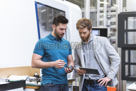 two men with tablet talking in