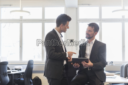 two businessmen standing in office discussing