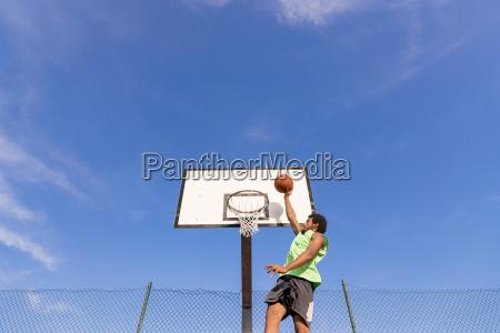 junger mann der basketball spielt