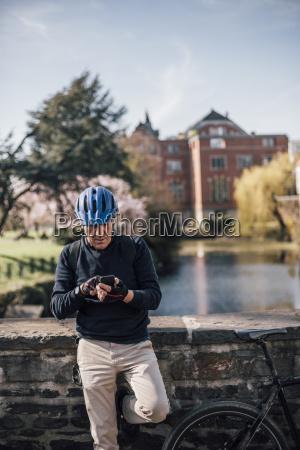 seniorenmann mit fahrradhelm mit smartphone
