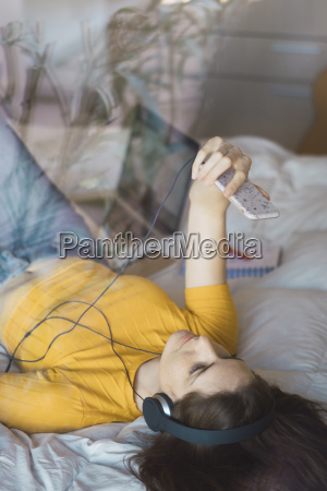 young woman with headphones lying on