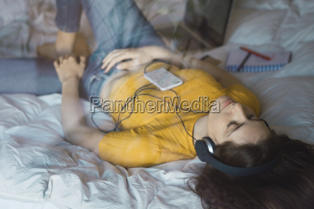 young woman lying on bed listening