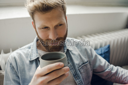 man relaxing at home drinking coffee