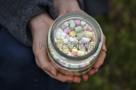 hands holding glass of marshmallows close