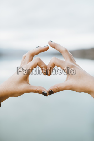 womans hands forming heart shape in