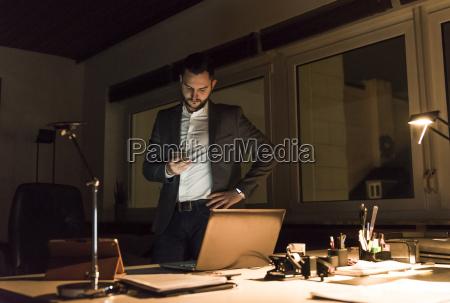 geschaeftsmann steht nachts mit smartphone im