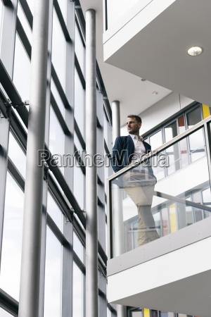 businessman in office building looking out
