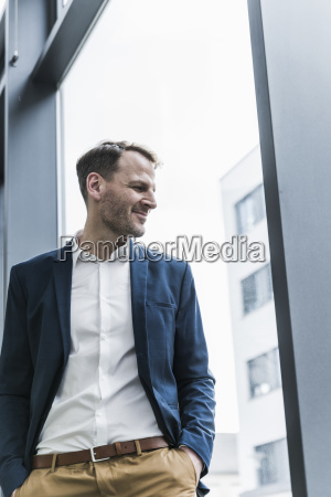 smiling businessman looking out of window