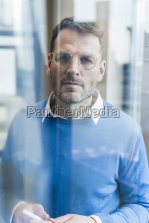 focused businessman looking at glass pane