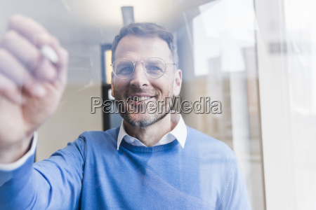 confident businessman writing on glass pane