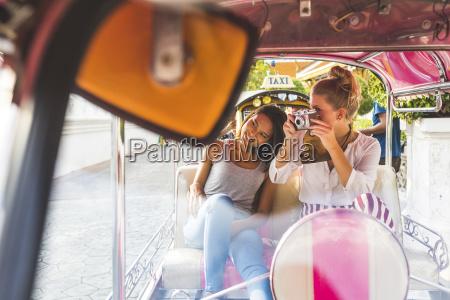 thailand bangkok two friends riding tuk