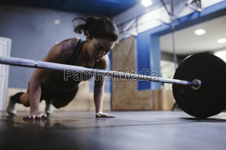 frau macht push ups bei langhantel