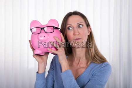 mature woman holding piggybank with eyeglasses