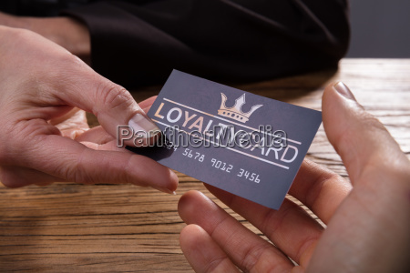 human hand giving loyalty card to