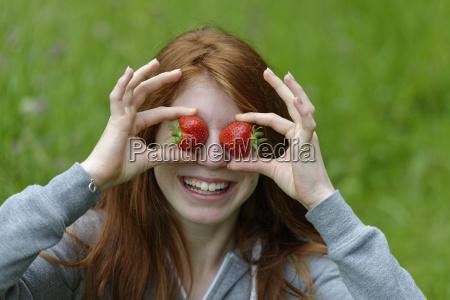 maedchen teenager mit erdbeeren vor den