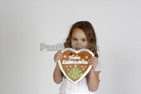 freches kind maedchen mit lebkuchenherz frohe