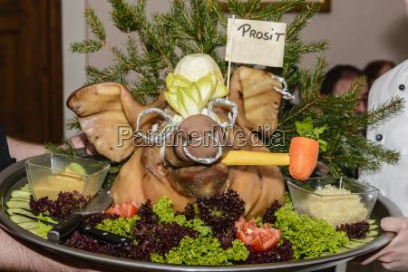 gekochter schweinskopf wird auf tablett serviert