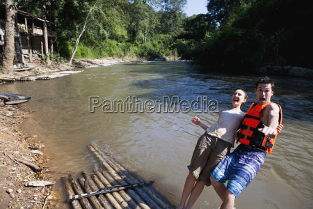young tourists bamboo rafting down the