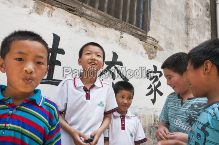 young boys playing beside their school